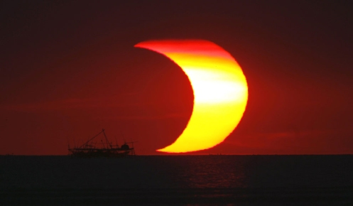 The moon passes in front of the sun, during a partial solar eclipse, as it sets over Manila Bay, in the Philippines on January 26, 2009