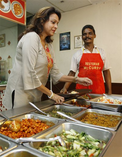 Wife of McCurry restaurant owner Kanageswary Suppiah, left, helps serve a meal as a staff member looks after a court victory over U.S. fast food giant McDonald's in Kuala Lumpur, Malaysia, Tuesday, Sept. 8, 2009.