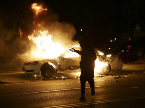 A man runs from a police car that is set on fire.