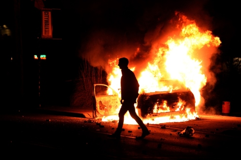 A man walks past a burning police vehicle during clashes between police and protesters over the decision in the shooting death 18-year-old Michael Brown.