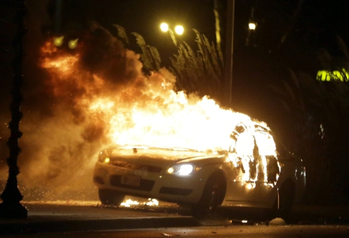 A police car is set on fire after a group of protesters vandalise the vehicle.