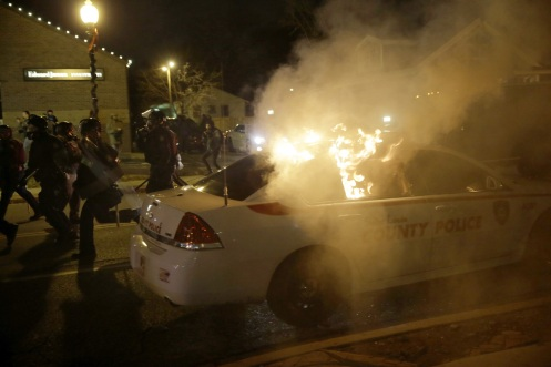 A police vehicle is vandalised and set on fire. (AP Photo-David Goldman)