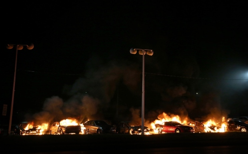 .A row of cars burn at a used car lot during a demonstration.