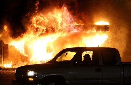 car drives by a burning building during a demonstration on November 25, 2014 in Ferguson, Missouri.