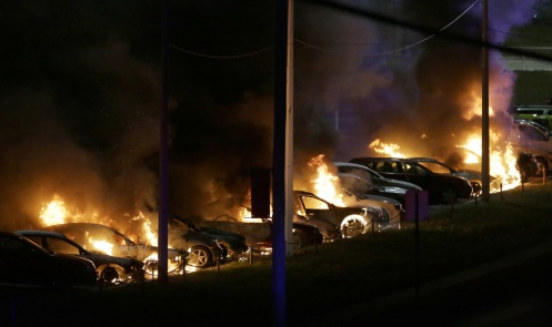 Cars burn at a dealership Tuesday, Nov. 25, 2014, in Dellwood, Mo.