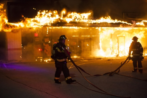 Firefighters attempt to put out a burning building during riots after grand jury's decision not to indict a police officer Darren Wilson.