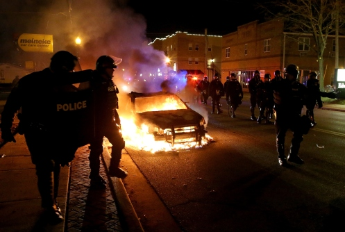 Police officers walk by a burning police car during a demonstration.