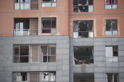 A couple check their belongings in their apartment after a blast destroyed all the windows. (Fred Dufour)