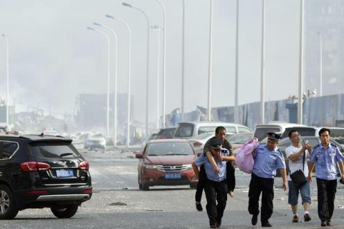 Chinese police help a man to safety on a highway near the explosion site. (Ng Han Guan)