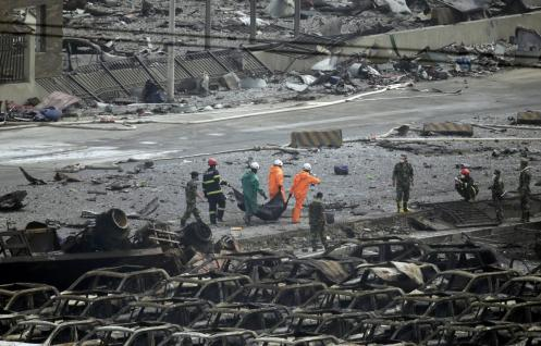Firefighters carry the body of a victim from the site of the explosions on Friday, Aug. 14. (Jason Lee)