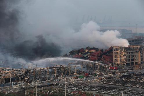Rescuers work among hundreds of burned cars and several destroyed buildings after a huge explosion rocked the port city. China's earthquake bureau said the magnitude of the second blast was equivalent to 21 tons of TNT. (Wu Hong)