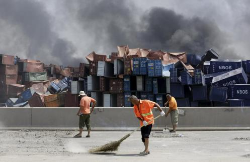 Workers clean debris form the road near the explosion site, where stacks of shipping containers had crumbled. (Jason Lee)